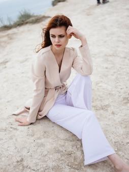 Mooie vrouw poseren in de buurt van rotsen in het zand model reizen