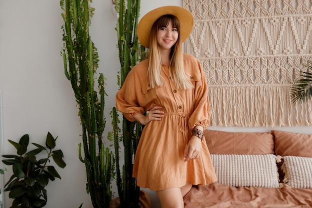 Mooie vrouw poseren in linnen jurk in haar slaapkamer