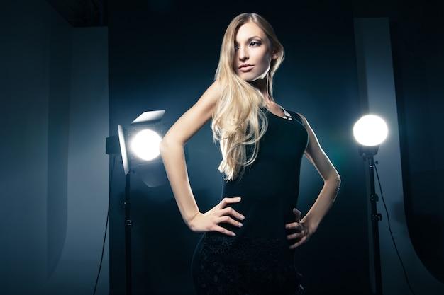 Mooie vrouw poseren in studio in lichtflitsen