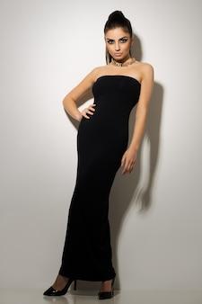 Mooie vrouw poseren in zwarte jurk