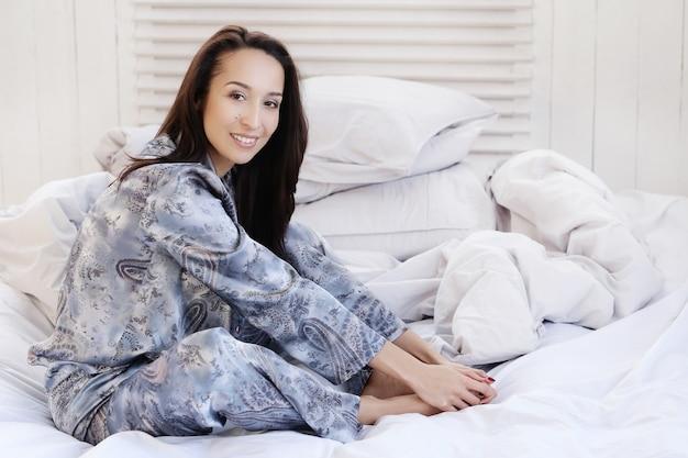 Mooie vrouw poseren liggend op het bed