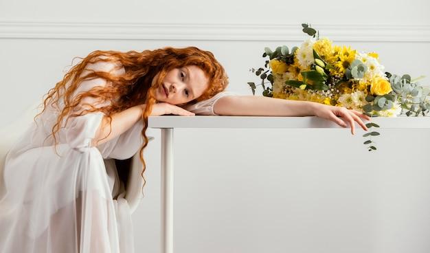 Mooie vrouw poseren met boeket van lentebloemen op tafel