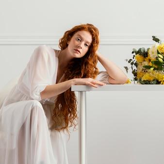 Mooie vrouw poseren met boeket van lentebloemen