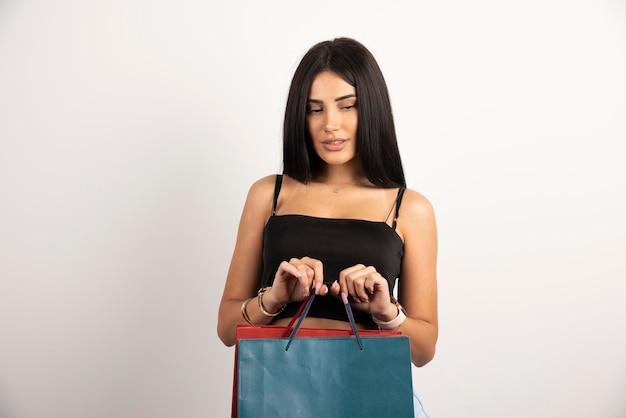 Mooie vrouw poseren met boodschappentassen op beige achtergrond. hoge kwaliteit foto