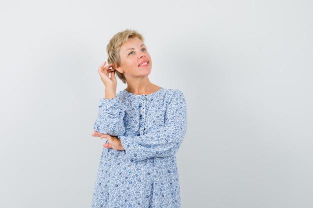 Mooie vrouw poseren met hand aanraken horen in blouse met patroon en op zoek charmant, vooraanzicht.