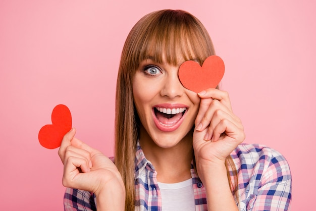Mooie vrouw poseren met papieren hart tegen de roze muur