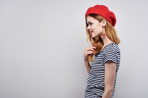 Mooie vrouw poseren mode aantrekkelijk uiterlijk rode oorbellen sieraden lichte achtergrond