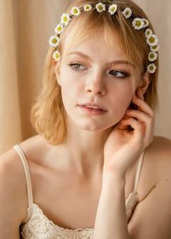 Mooie vrouw poseren terwijl het dragen van een kroon van lentebloemen