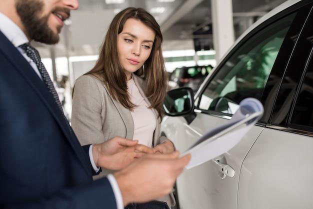 Mooie vrouw praten met autoverkoper
