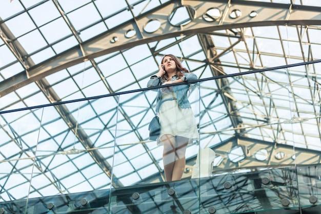 Mooie vrouw praten op mobiele telefoon op luchthaven met glazen plafond