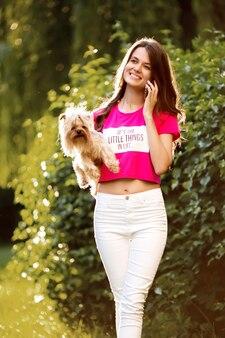 Mooie vrouw praten over de telefoon tijdens het wandelen met een hond in het park