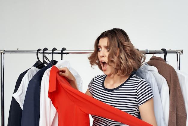 Mooie vrouw probeert op een rood shirt geïsoleerde background