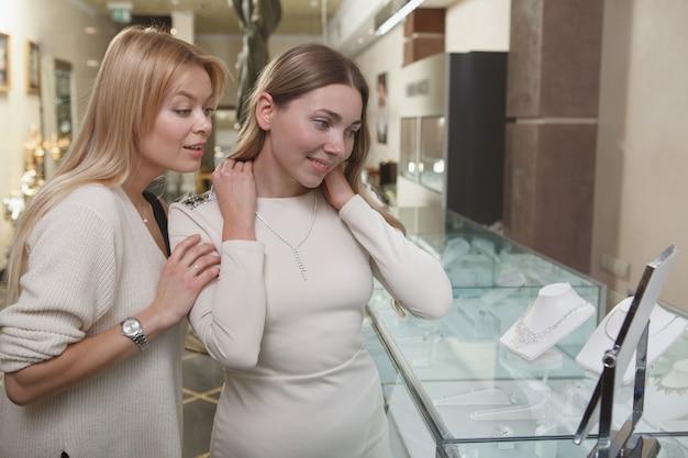 Mooie vrouw probeert op ketting, winkelen met haar vriend bij juwelier