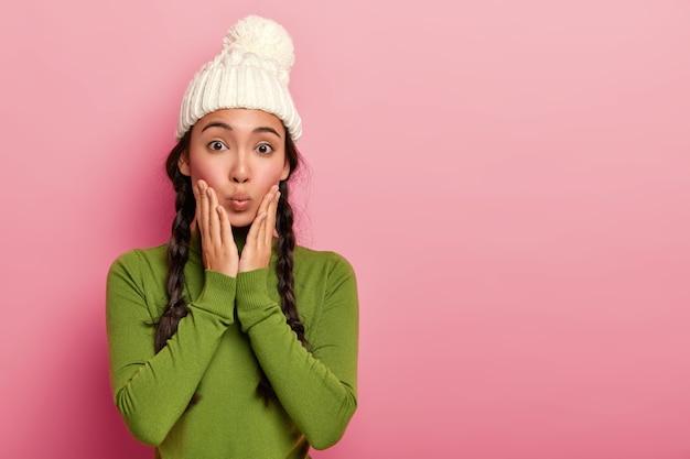 Mooie vrouw raakt wangen, heeft afgeronde lippen, heeft twee vlechten, draagt witte wintermuts, groene coltrui tegen roze achtergrond
