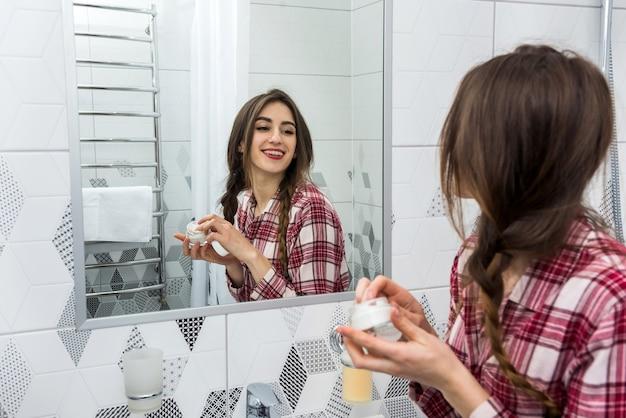 Mooie vrouw reinigende hydraterende huidcrème op gezicht na bad toe te passen. huidverzorging Premium Foto