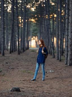 Mooie vrouw reist in het bos met een rugzak op haar rug en in een blauw shirt.
