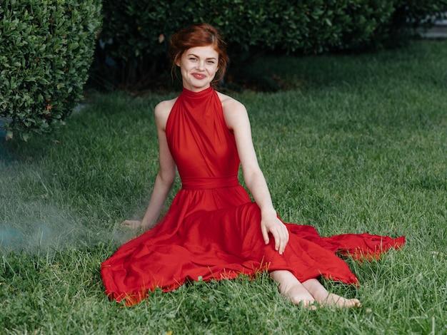 Mooie vrouw rode jurk glamour natuur groen gras luxe. hoge kwaliteit foto