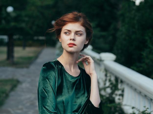 Mooie vrouw rode lippen glamour natuur groene jurk luxe model.