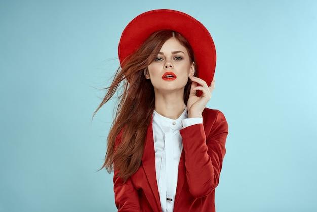 Mooie vrouw rode pak hoed emoties lichte make-up studio