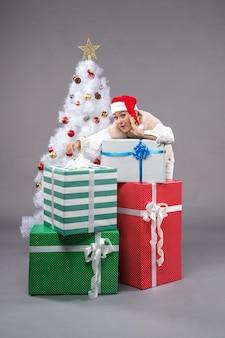 Mooie vrouw rond cadeautjes op grijs