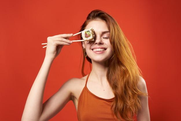 Mooie vrouw roodharige vrouw sushi eetstokjes dieet voedsel rode achtergrond