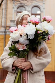 Mooie vrouw ruiken een boeket bloemen buitenshuis
