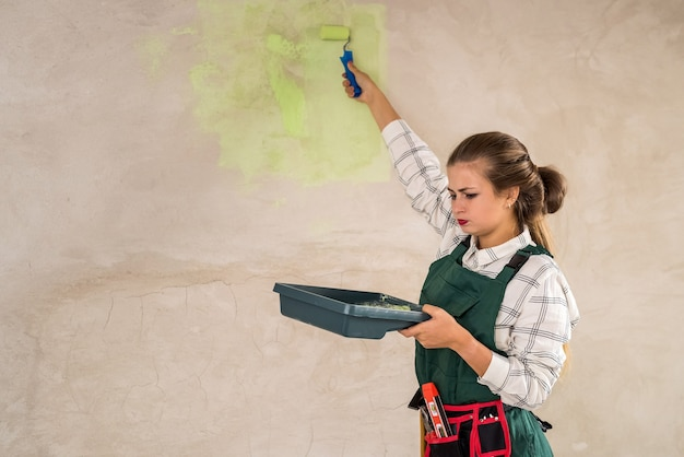 Mooie vrouw schilderen muren met dienblad en roller
