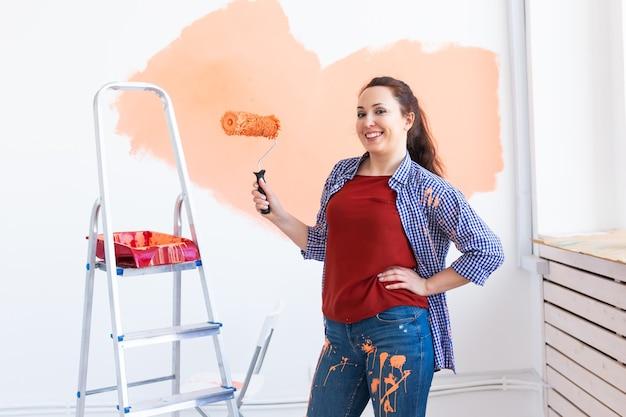 Mooie vrouw schilderij muur in haar nieuwe appartement. renovatie en herinrichting concept.