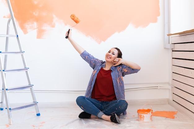Mooie vrouw schilderij van de muur met verfroller. portret van een jonge mooie vrouw schilderij