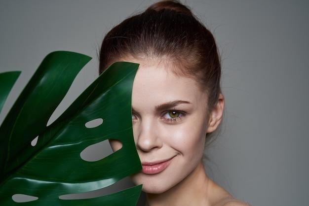 Mooie vrouw schone huid palmblad gezondheid cosmetica donkere achtergrond