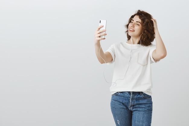 Mooie vrouw selfie te nemen tijdens het luisteren naar muziek in oortelefoons