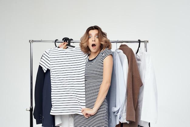Mooie vrouw shopaholic die kleren kiest die in de winkel geïsoleerde achtergrond winkelen