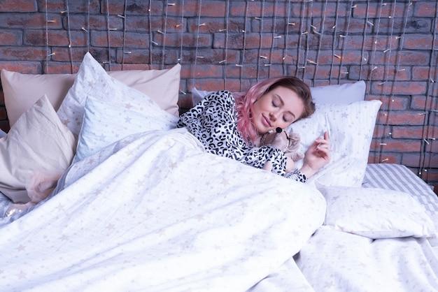 Mooie vrouw slaapt hard op het bed met haar tilda-speelgoed