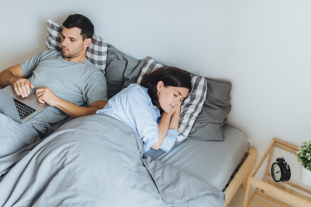 Mooie vrouw slaapt in bed, ziet aangename dromen, terwijl haar man op een laptop werkt.