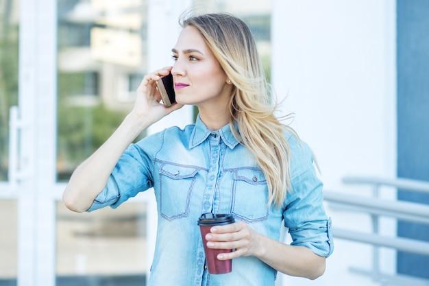 Mooie vrouw spreekt aan de telefoon en drinkt koffie