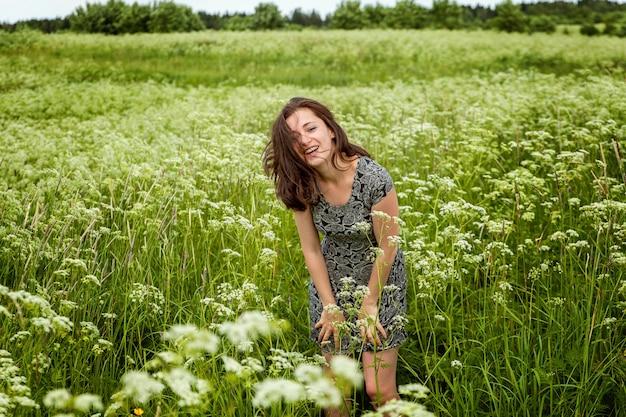 Mooie vrouw springen op zomer veld met bloeiende wilde bloemen