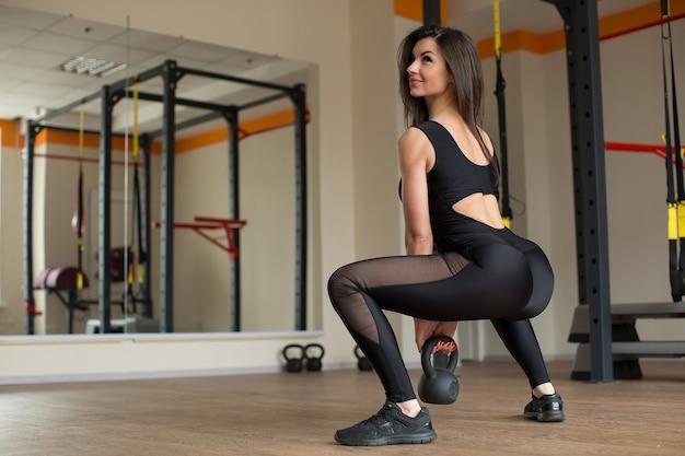 Mooie vrouw squats met kettlebell in de sportschool