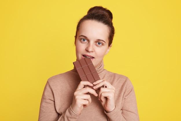 Mooie vrouw staande geïsoleerd over gele muur en bijtende reep chocola, voelt honger, draagt een casual beige trui, heeft donker haar en haarknot.