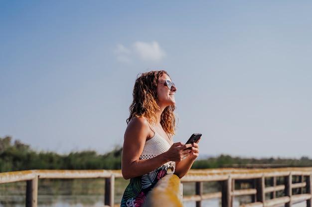 Mooie vrouw staande op een houten pier en het gebruik van mobiele telefoon