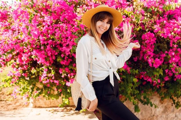 Mooie vrouw staande op roze bloemen dragen strooien hoed en casual outfit.