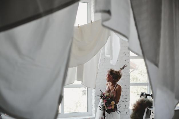 Mooie vrouw staat met een boeket onder opknoping wasserij in de kamer