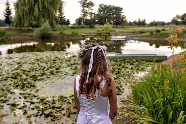 Mooie vrouw staat voor een vijver in de prachtige tuin