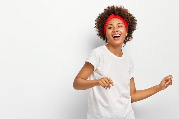 Mooie vrouw staat zijwaarts, voelt energiek dansen actief op muziek draagt rode hoofdband casual wit t-shirt vormt binnen