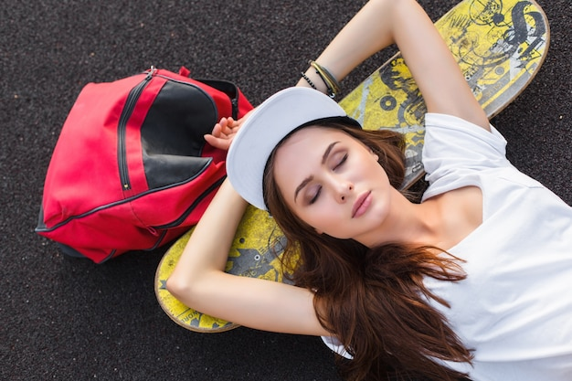 Mooie vrouw straat stedelijke stijl poseren buiten op de speelplaats met skateboard en reizen rugzak