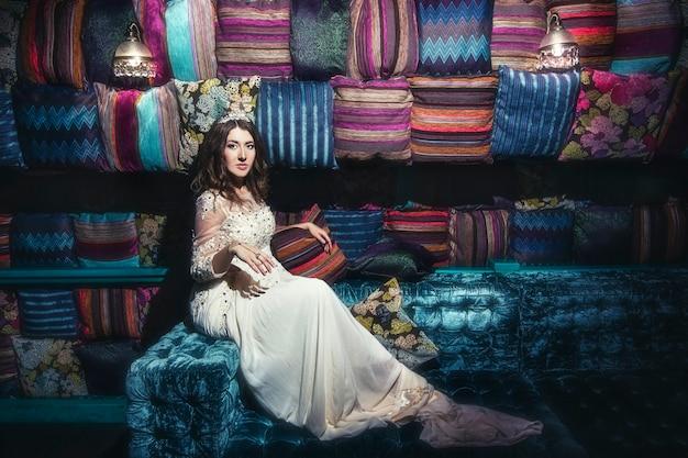 Mooie vrouw sultana jurk sieraden tiara in de oosterse stijl en het interieur