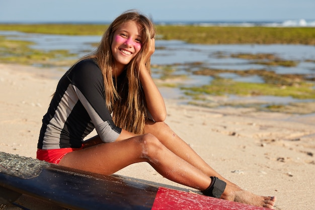 Mooie vrouw surfer gekleed in badpak, heeft beschermende branding zink op gezicht