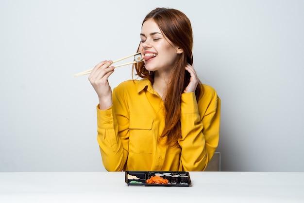 Mooie vrouw sushi eten