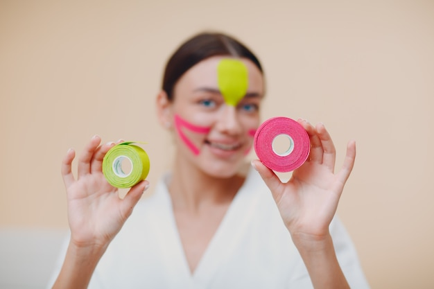 Mooie vrouw tape opheffing behandeling op gezicht toe te passen
