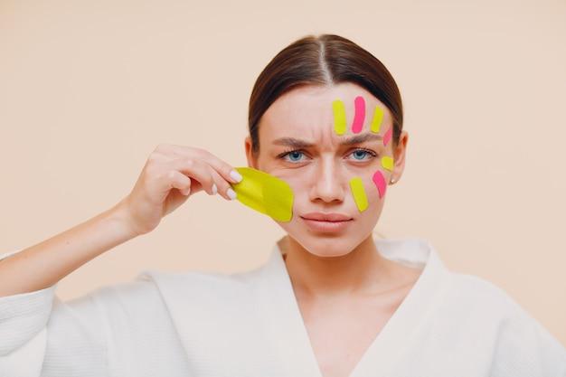 Mooie vrouw tape opheffing behandeling op gezicht verwijderen toe te passen