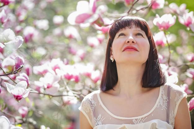 Mooie vrouw tegen de achtergrond van magnolia bloemen.